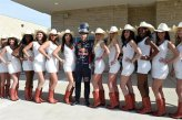 Sebastian Vettel (GER) Red Bull Racing poses with his helmet perched on his head and the US grid girls.